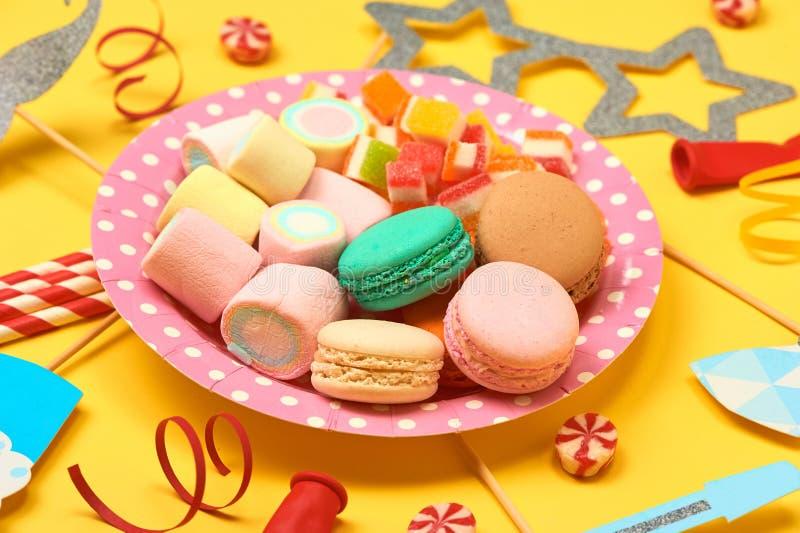 五颜六色的甜点 棒棒糖、蛋白杏仁饼干、蛋白软糖、橘子果酱、巧克力和糖果 与空间的顶视图您的问候的 图库摄影