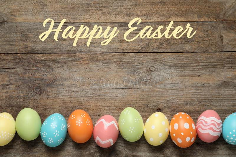 五颜六色的被绘的鸡蛋和文本复活节快乐的平的被放置的构成 免版税库存照片