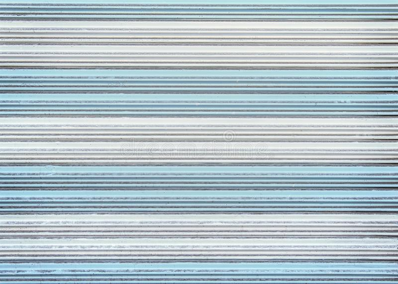五颜六色的老白色和蓝色滚动的钢门纹理或路辗快门门的样式背景的 免版税库存图片