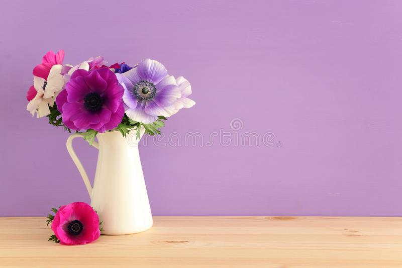 五颜六色的银莲花属春天花束在花瓶的在木桌 库存图片