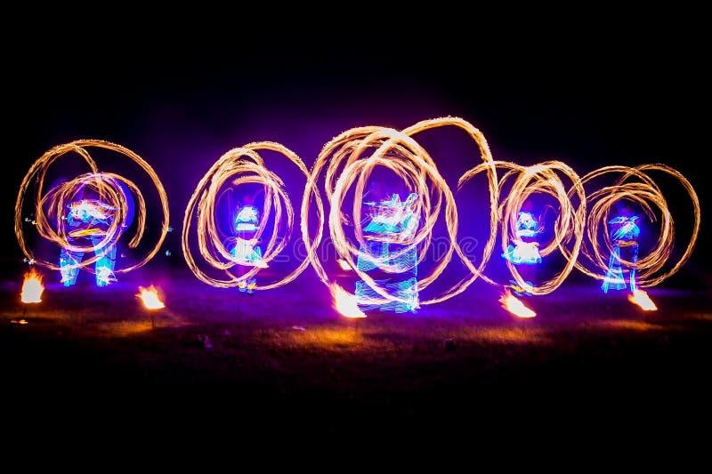 令人惊讶的火展示舞蹈 使用与五颜六色的火焰的美丽的服装的火舞蹈家 库存图片