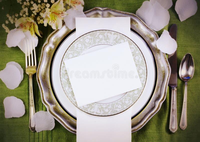 以与liliies,在一个选材台上的丝绸花瓣的结婚宴会的餐位餐具混杂的老和现代样式为特色 免版税库存图片