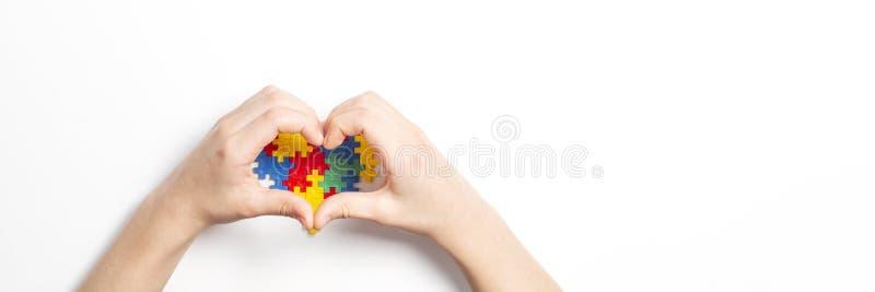 以心脏和五颜六色的心脏的形式孩子手由塑料建筑难题片断做成在白色背景 世界 免版税库存图片