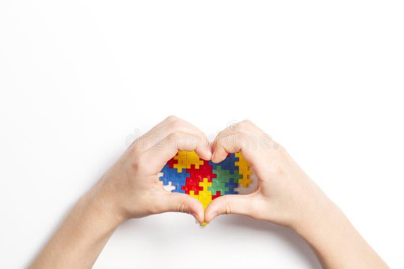 以心脏和五颜六色的心脏的形式孩子手由塑料建筑难题片断做成在白色背景 世界 库存照片
