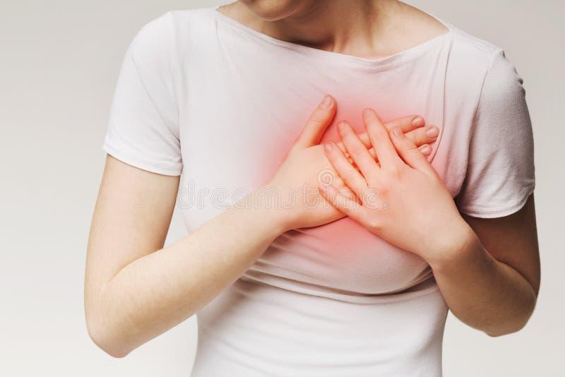 从严重胸口痛的年轻女性痛苦 免版税图库摄影