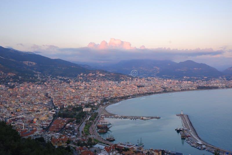 从上面的看法在海港口城市阿拉尼亚,土耳其 山围拢的海湾,在蓝色的山和桃红色云彩 图库摄影