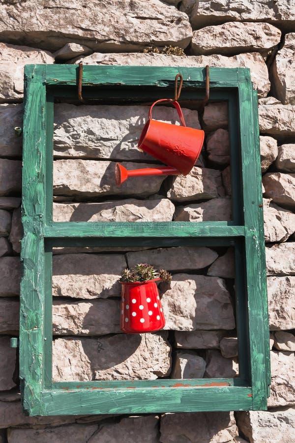 从一个老窗架、喷壶和水罐的设施有在一个石墙上的一棵植物的在一好日子 免版税库存照片