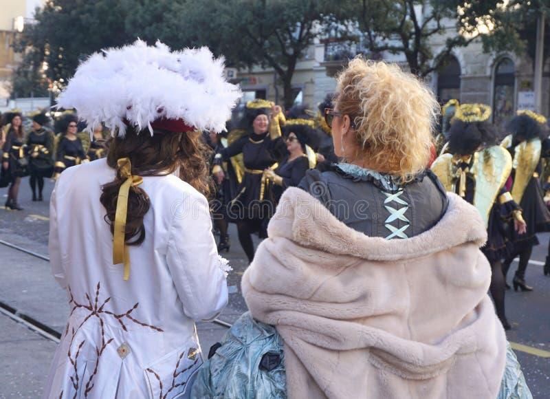 从后面的被打扮的夫妇,在狂欢节队伍的街道上 库存图片