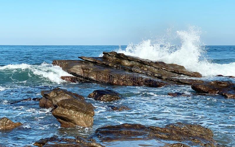 从海的水飞溅击中在海滩的岩石 免版税库存图片