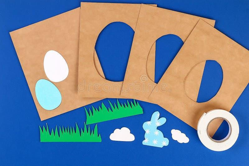 从纸的Diy复活节卡片 容量与兔宝宝,在蓝色背景的鸡蛋的贺卡 3d 免版税库存照片