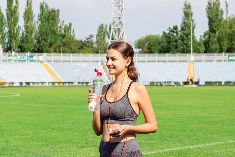 从瓶的少女饮用水在跑在体育场以后 体育和健康概念 妇女有音乐的藏品电话 免版税库存图片