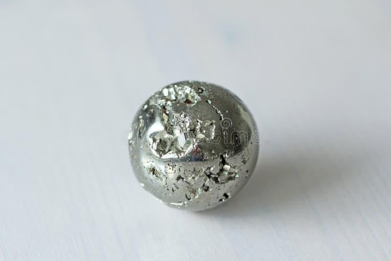 从自然硫铁矿的美丽的铁球 在一个空白背景 金黄和金黄球或硫铁矿球形 自然石头 免版税库存图片