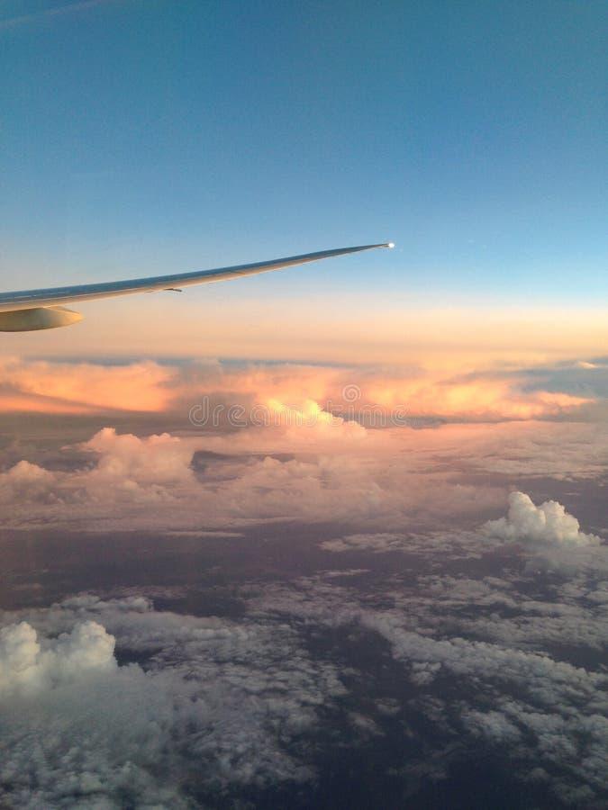 从飞机的窗口的看法对翼和意想不到地美好的日落的在云彩上 免版税库存图片