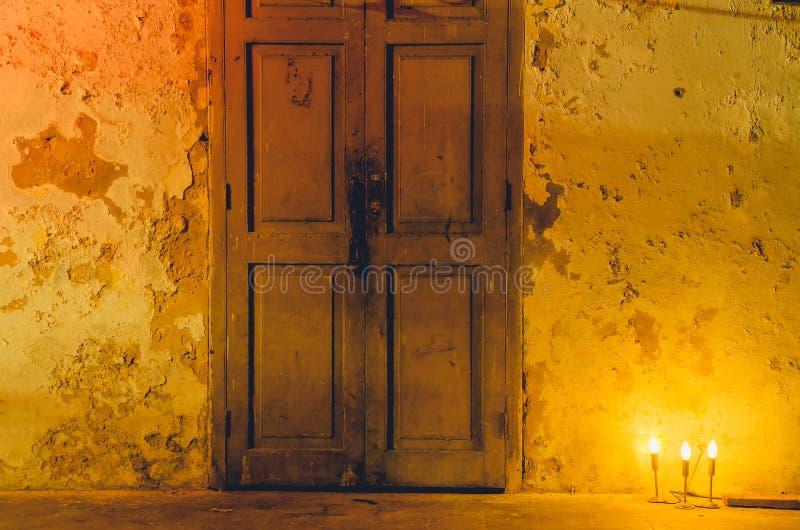 从黑灯的橙色光是前面的在有黑污点在夜和拷贝空间的老白色肮脏的墙壁上 免版税库存图片