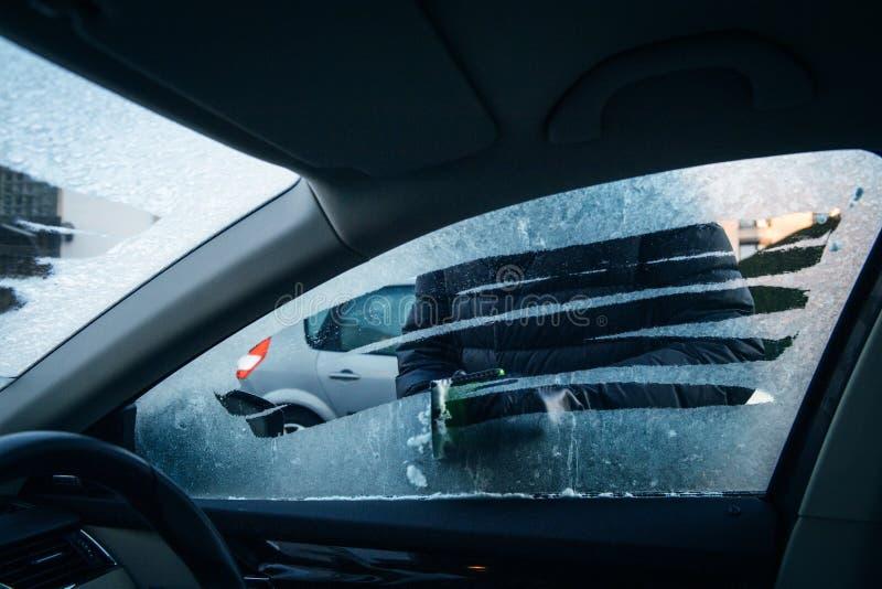 从霜的妇女清洗的汽车司机窗口与冰霜刮板 免版税库存照片