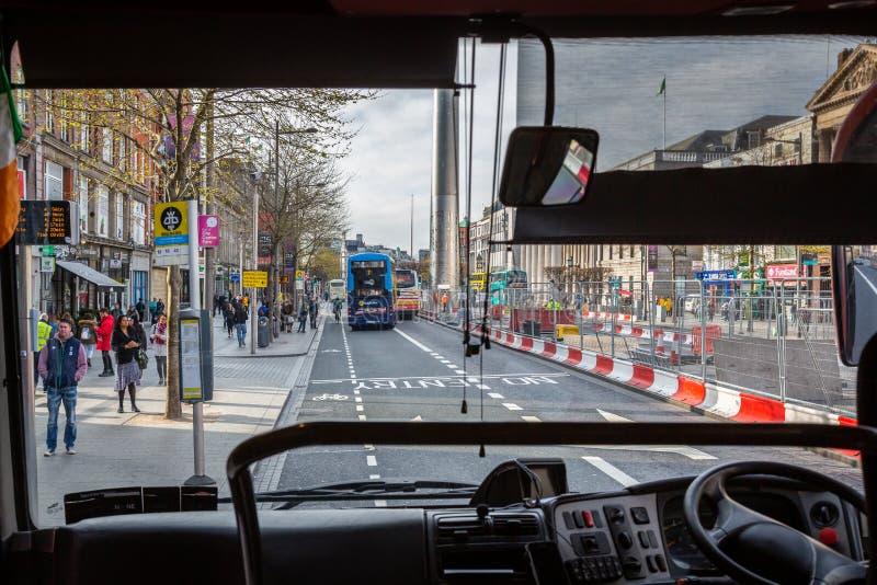 从里面看见的一条繁忙的城市街道的公交司机透视 免版税库存图片