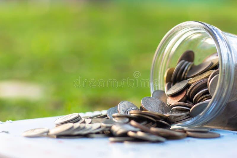 从金钱玻璃瓶子溢出的硬币 免版税库存图片