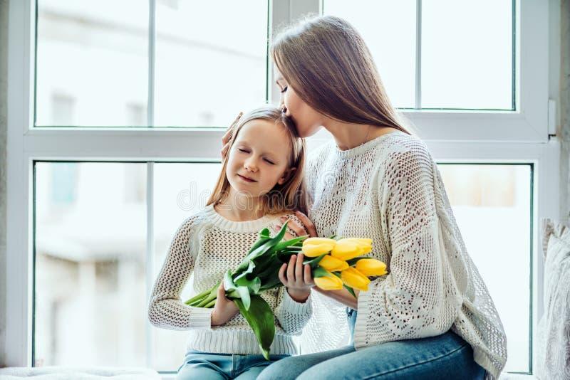 他们互相珍惜 爱的母亲和女儿在家坐窗口基石 免版税库存照片