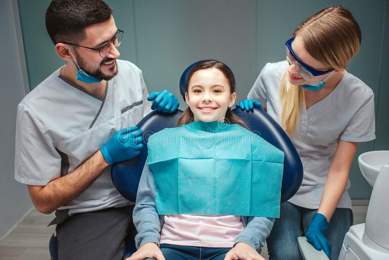 仔细的正面男性和女性牙医看看孩子患者和微笑 女孩在牙齿椅子坐 她看起来平直和 库存图片