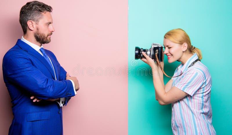他的信心是她的焦点 摄影师射击的男性模型在演播室 摆在女性前面的商人 免版税图库摄影