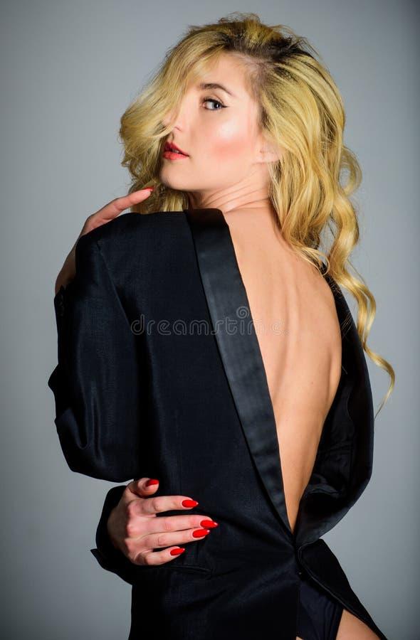 他的夹克适合我 在赤裸身体的女孩嬉戏的金发碧眼的女人佩带的男性夹克 如此感觉在男性衣裳 免版税库存照片