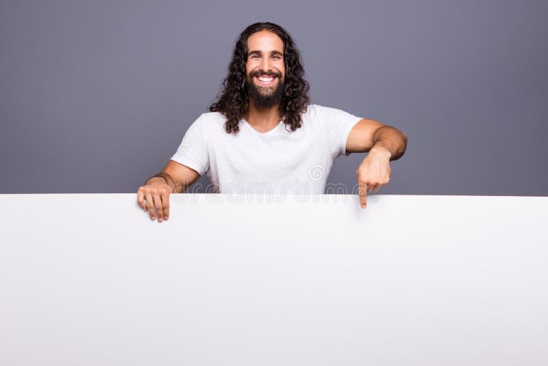 他的画象他举行在手大拷贝空间促进的好英俊的可爱的快乐的爽快有波浪头发的人 免版税库存照片