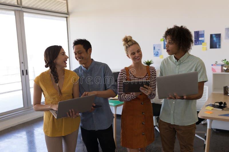 企业同事谈论在膝上型计算机和数字片剂在办公室 库存图片