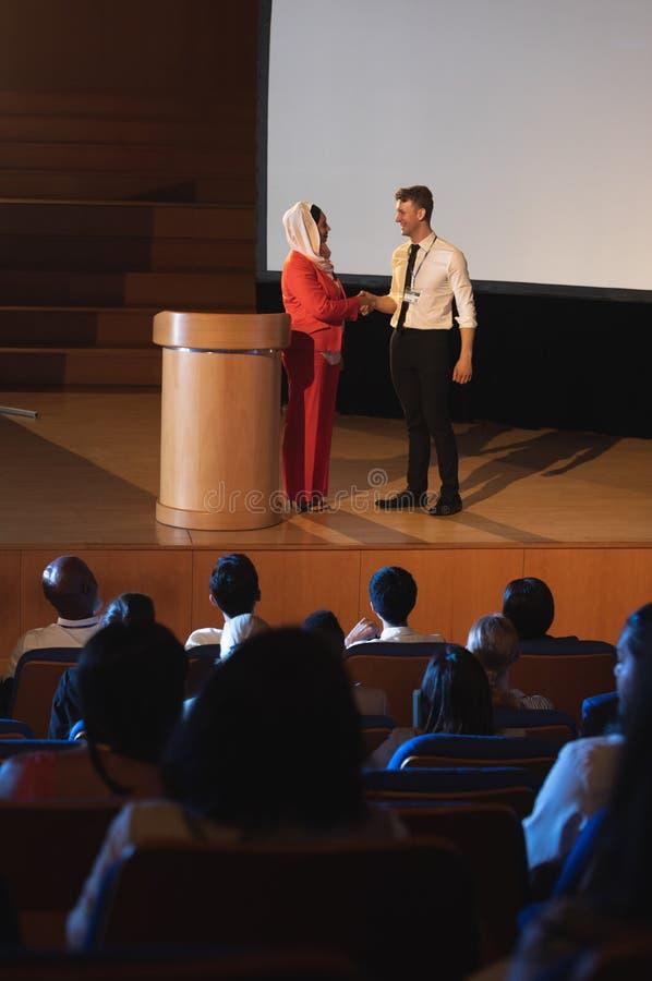企业同事身分和谈论互相在观众前面在观众席 免版税库存图片