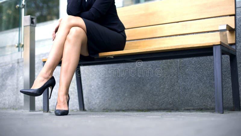 企业夫人坐长凳,与伙伴的等待的会谈在街道上 库存图片