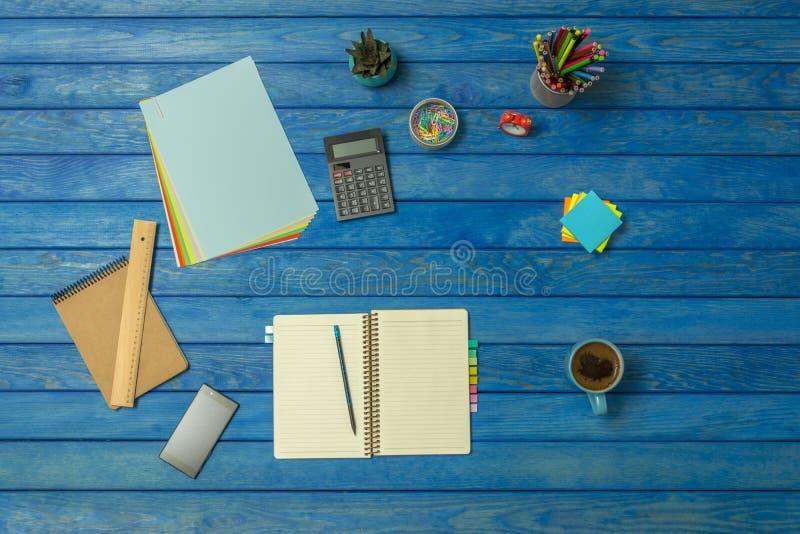 企业工作场所和事务蓝色木办公桌表反对顶视图 免版税库存图片