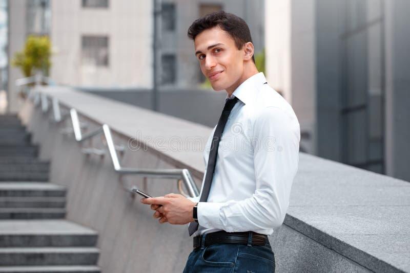 企业生活方式 倾斜在城市街道上的墙壁的商人有看照相机的智能手机的好奇 免版税图库摄影