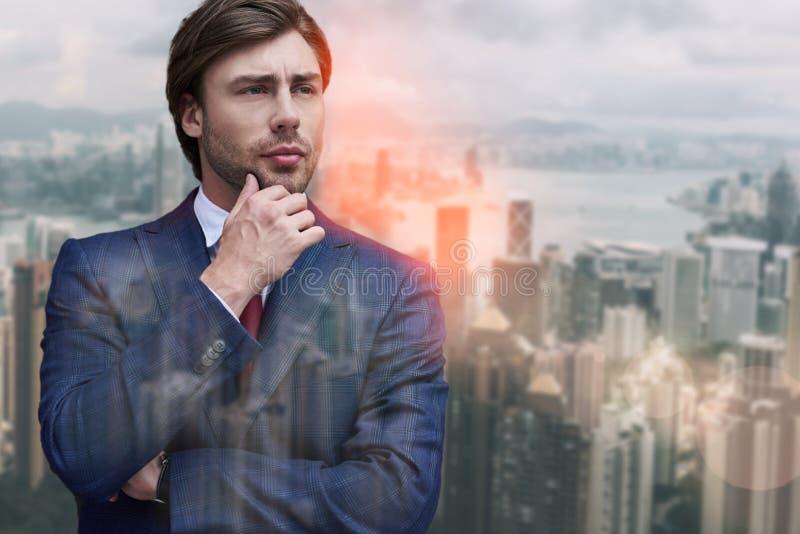 企业认为 看英俊的有胡子的商人接触他的下巴和,当站立反对时 库存照片