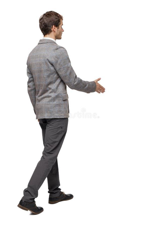 伸他的握手的手的后面观点的一个走的商人 免版税库存图片