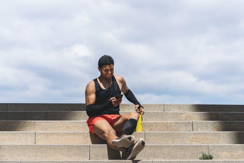 休息在他的锻炼以后和使用手机的愉快的肌肉适合的体育人短跑选手 免版税图库摄影