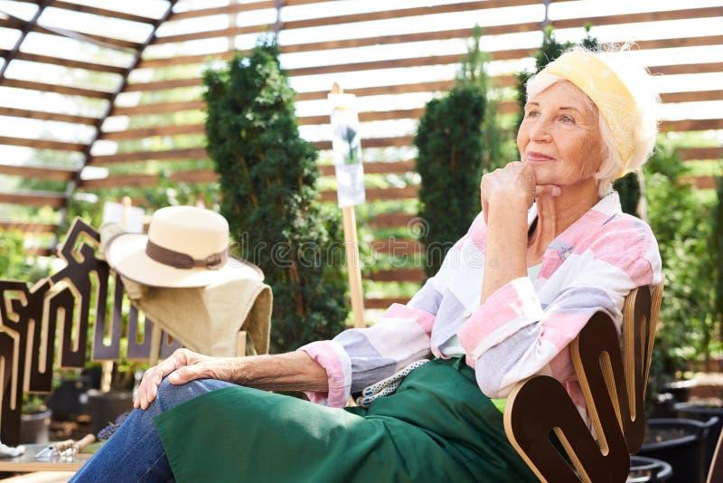 休息在庭院里的沉思资深妇女 免版税库存图片