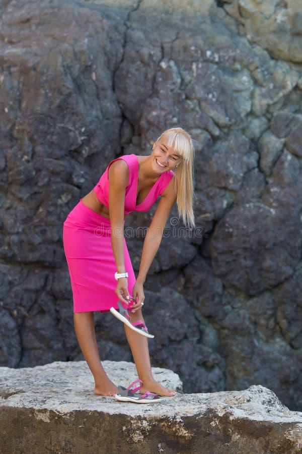 休息在狂放的岩石海滨偏僻的地方的被晒黑的金发女性  图库摄影
