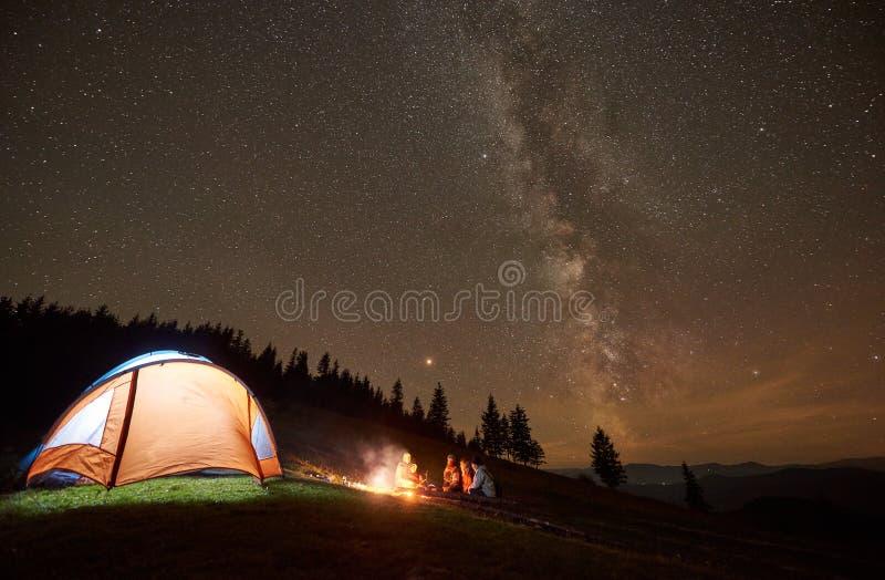 休息在阵营,营火旁边的朋友在夜满天星斗的天空下 图库摄影