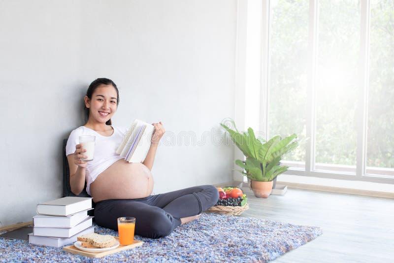 休息和读书的亚裔美丽的孕妇,当坐地板在客厅时 免版税库存图片