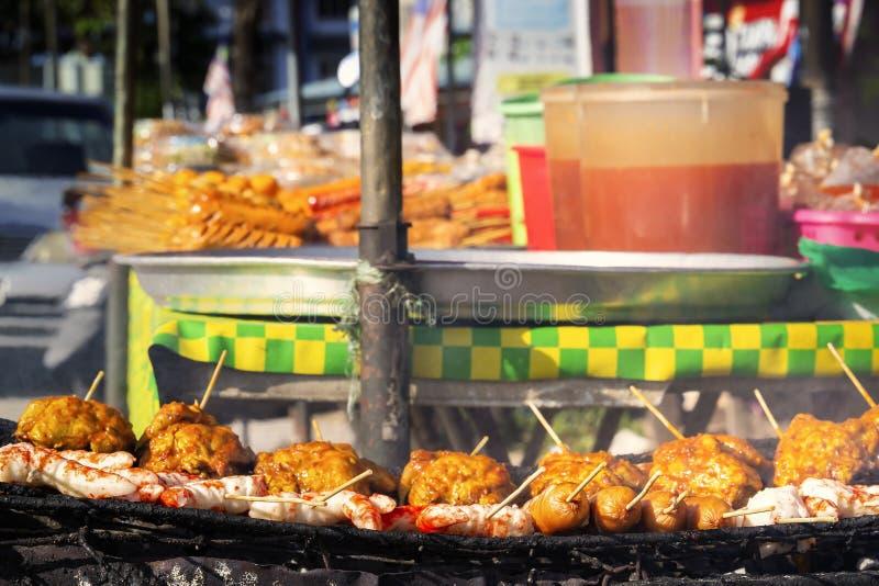 传统亚洲食物鸡翅、虾和香肠在木串- satay在柜台附近被烤用街道食物 库存照片