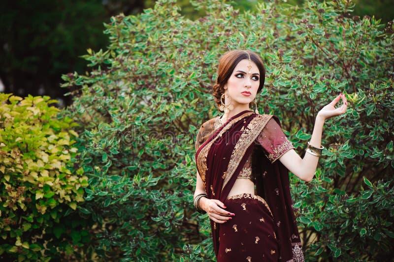 传统印度衣物莎丽服的美丽的年轻白种人妇女有新娘构成和首饰和无刺指甲花纹身花刺的 免版税库存照片