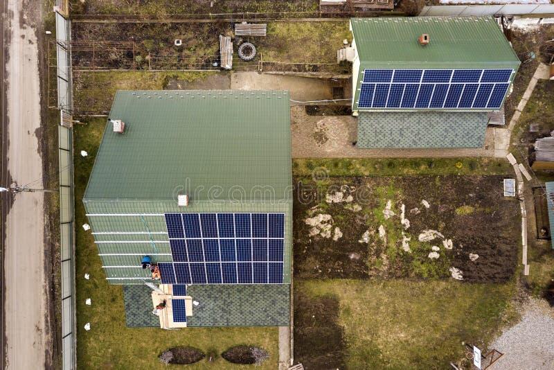 住宅房子空中顶视图有安装太阳照片流电盘区系统的工作者队的在屋顶 可延续的能源 免版税库存照片