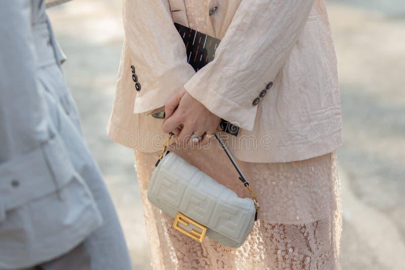 佩带一件米黄色的礼服和一个白色提包的模型Fendi 免版税库存照片