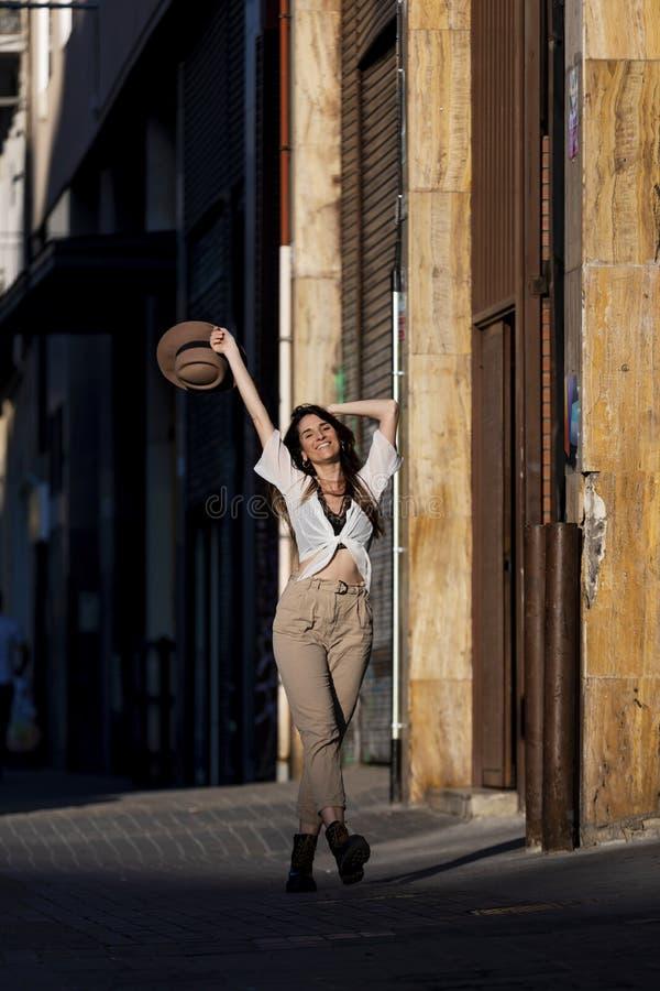 佩带便衣的一美丽的时髦年轻女人的正面图站立在拿着帽子的街道,当看在a时的照相机 免版税图库摄影
