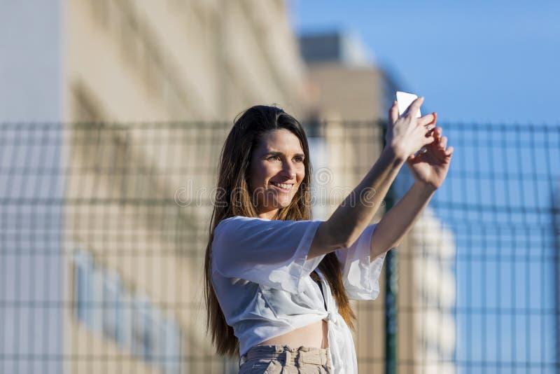 佩带便衣的美丽的时髦年轻女人正面图站立在街道,当采取微笑在一好日子时的selfie 免版税库存图片