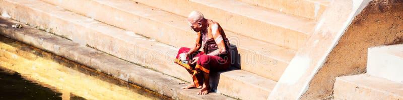 佩带典型的长袍选址的老人在Sree Padmanabhaswamy寺庙水池在晴天期间在特里凡德琅,印度 免版税库存图片