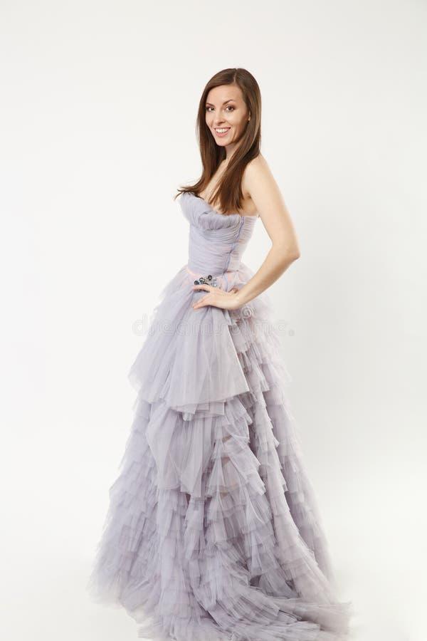 佩带典雅晚礼服紫色褂子摆在的全长照片时装模特儿妇女隔绝在白色墙壁背景 库存照片