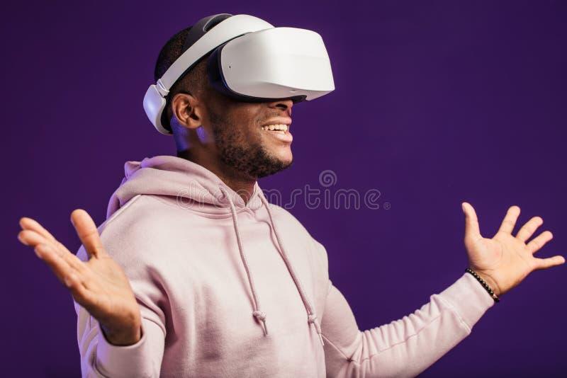 佩带虚拟现实风镜的非洲人隔绝在黑暗的紫色背景 库存照片