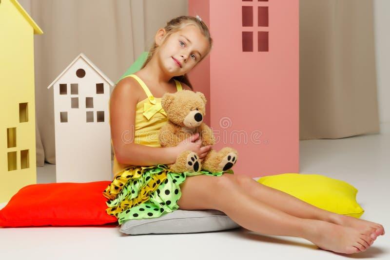 使用与一个玩具熊的女孩在玩具木房子里 免版税库存图片