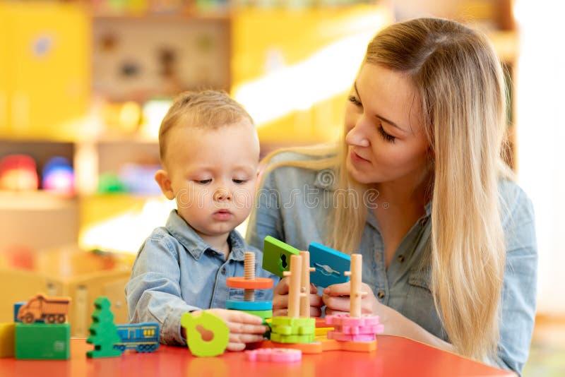 使用与孩子的婴孩指示装置在托儿所 库存图片