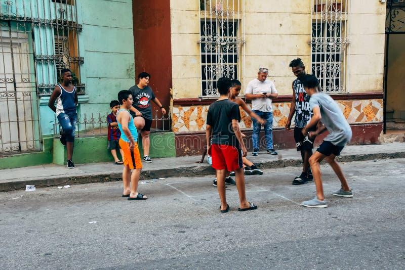 使用与在哈瓦那,古巴小街上的一个球的地方孩子  免版税库存图片